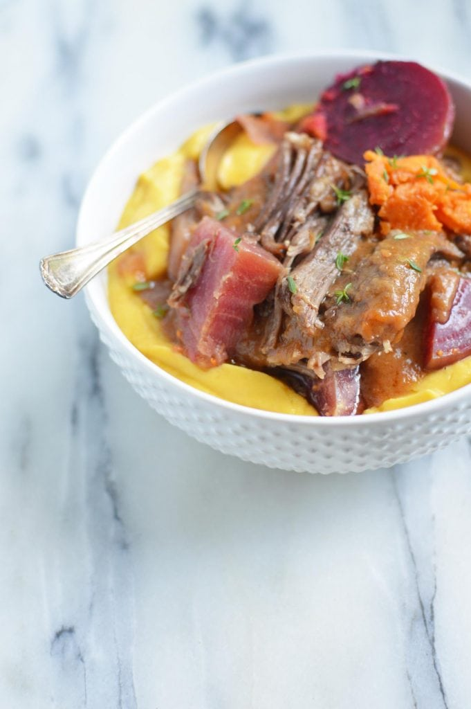 Instant Pot Short Ribs with Vegetables, short ribs with veggies in a white bowl with spoon sitting on a white and grey marble table top.