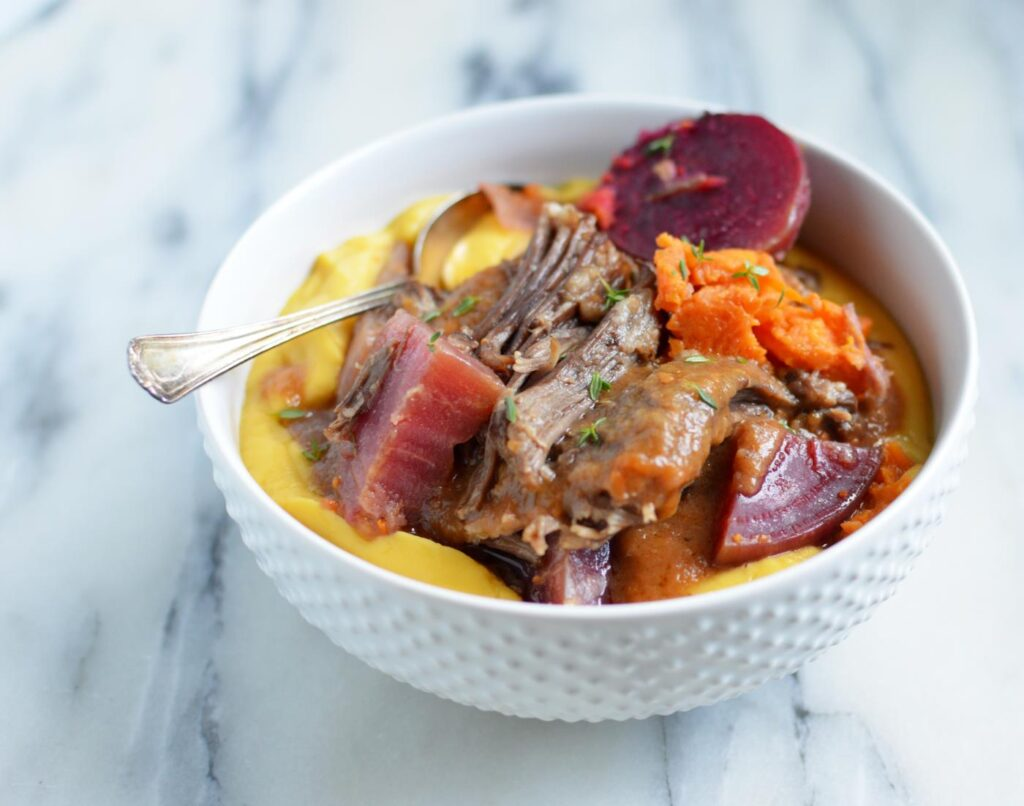Instant Pot Short Ribs with Vegetables in a white bowl with spoon sitting on top of a white and grey marbled table top