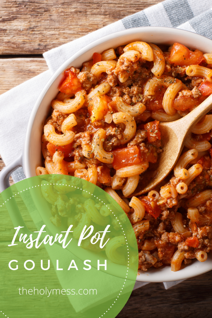 Instant Pot Goulash in a white serving platter with wooden spoon, kitchen towel and sitting on a wooden table top