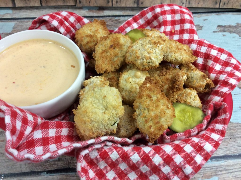 Air Fryer Fried Pickles in a red and white towel in a red basket with a dipping sauce