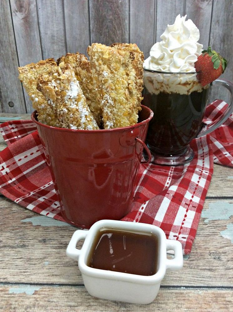 Air Fryer French Toast Sticks ready to serve in a red bucket with ice coffee on a table with a red towel