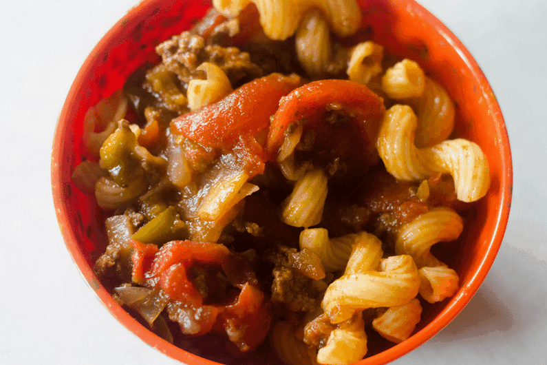 Instant Pot Goulash is a hearty dinner. Instant Goulash in red bowl on white table