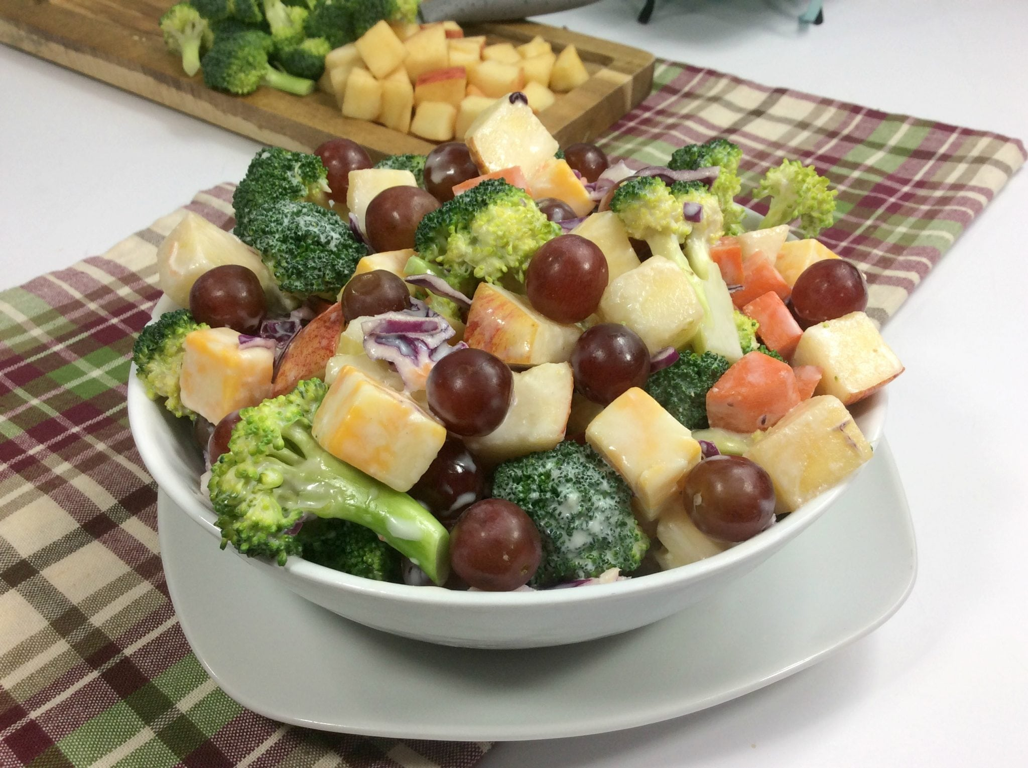 Weight Watchers broccoli salad in a white bowl on top of plaid towel