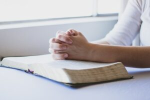 hands on Bible praying