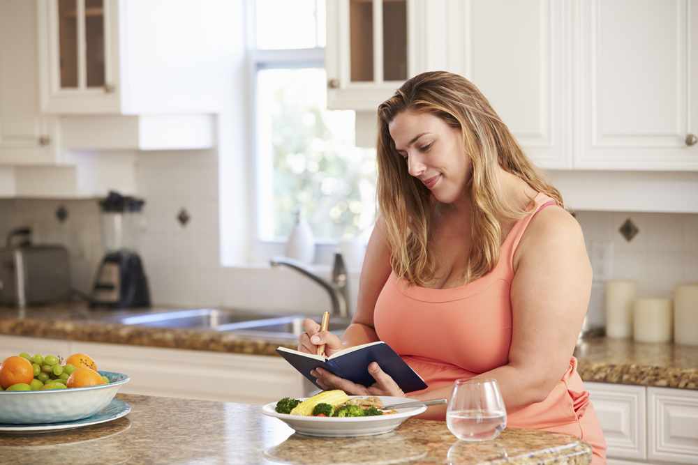 Women keeping a food log for weight loss with calorie counting.