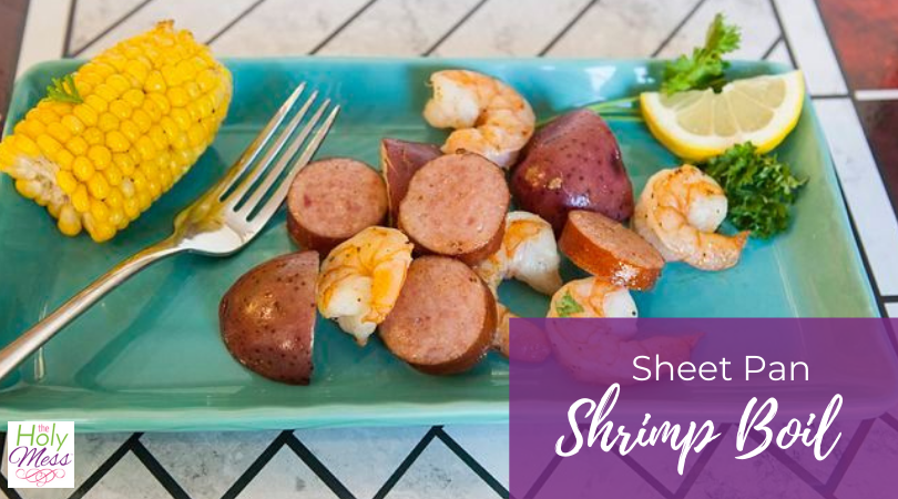 sheet pan shrimp boil on a blue plate with fork