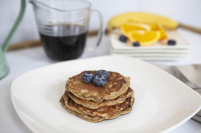 Weight Watchers banana pancakes on white plate with a drink and fruit
