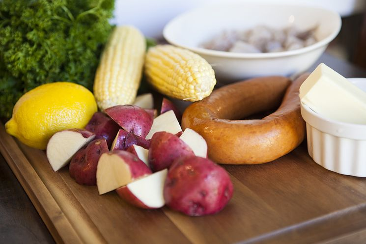 Ingredients for a sheet pan shrimp boil on a wooden cutting board.
