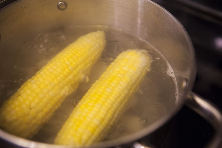 potatoes and corn boiling in a silver pot for a shrimp boil
