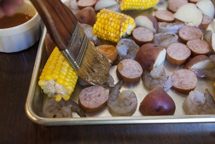 corn, sausage, shrimp on a metal sheet pan for the shrimp boil
